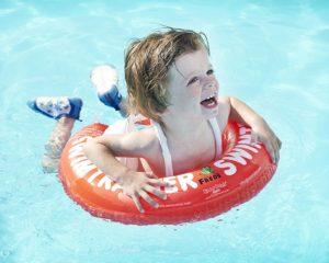 Kind schwimmt mit Schwimmring Freds Academy